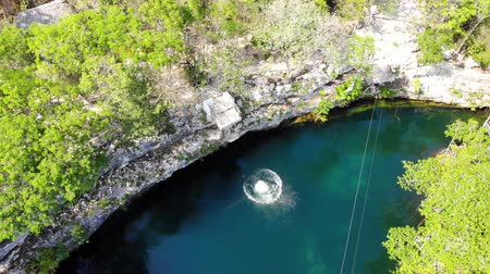 пресноводный : Aerial view of a guy jumping into a freshwater cenote, Quintana Roo, Mexico Стоковые видеозаписи