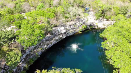 nadador : Aerial view of a guy jumping into a freshwater cenote, Quintana Roo, Mexico Stock Footage