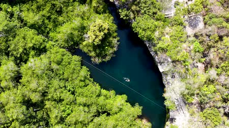 Aerial view of a guy swimming in a freshwater cenote, Quintana Roo, Mexico