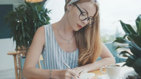 jornalismo : Young beautiful blonde woman daydreaming and writing in her journal, diary. Female write in notebook in cafe. Stock Footage