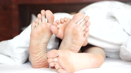 кровать : Pair of feet playing footsie under the covers at home in bed Стоковые видеозаписи