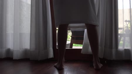 unveil : Close-up of legs of woman in bathrobe unveil curtain, standing near the window in home.