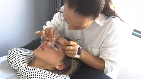 cílios : Professional master make long lashes holding out a pair of tweezers. Eyelash extension in beauty studio. Vídeos