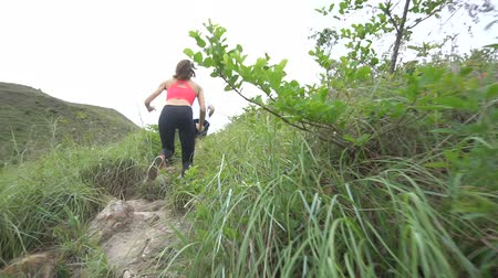 rekreasyon : Sporty boy and girl running on difficult high mountain track. Woman and man work out in nature