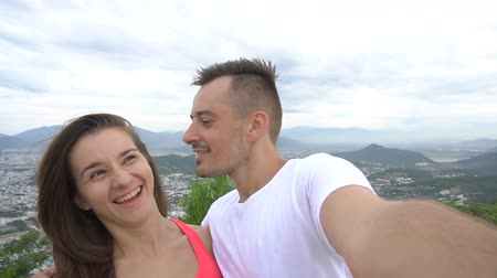 selfie girl : Smiling couple recording video, taking selfie in the mountains. Man kisses girl
