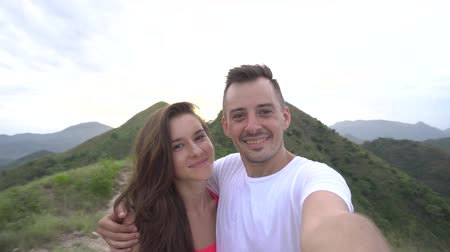 felicidade : Young couple taking selfie, laughing and go round in the mountains with beautiful aerial city view at sunset, enjoy the nature and carefree life