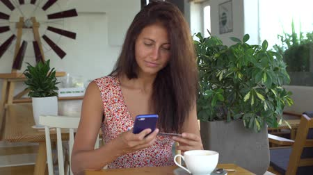 Woman using smartphone with credit card for shopping online in cafe Vídeos