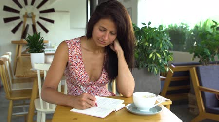 Young woman writer writes a book in cafe.