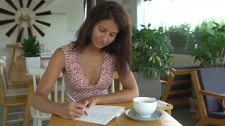 Woman writes in notepad in cafe. Vídeos