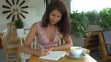 Female college student writing in notepad with pen