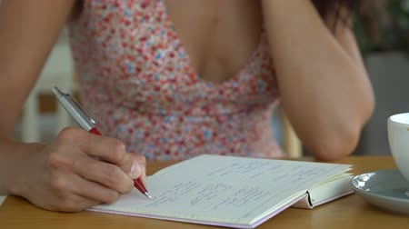 Woman writes poem in notepad in cafe. Vídeos