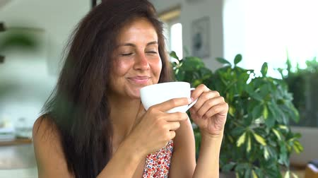 Beautiful happy woman drinking coffee and smiling. Vídeos