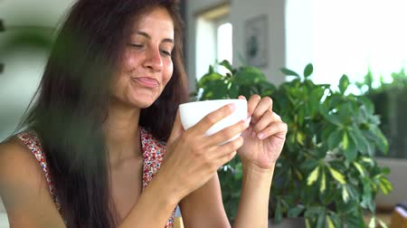 Woman relaxing, smiling and drinking coffee Vídeos