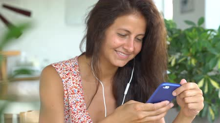 Female talking on phone smiling. Woman is speaking using white headphones.