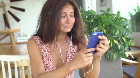 Girl speaks on her smartphone using headphones.