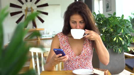 Beautiful young female working on smartphone in cafe.