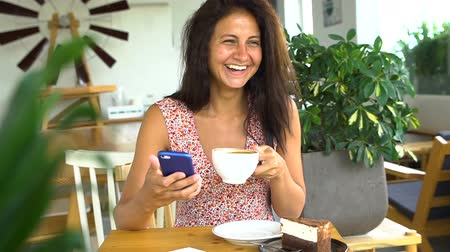 Woman using app on smartphone in cafe drinking coffee and laugh