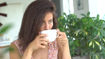 Young woman drinking coffee in cafe. Vídeos