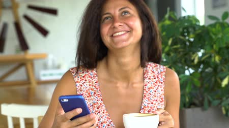Woman reading message on smartphone, drinking coffee and laugh
