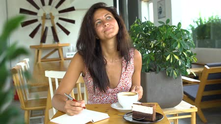 Young woman writing diary in her journal and drink coffee