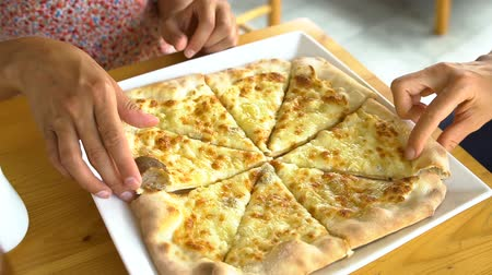 Close up of women taking cheese pizza slices from small plate Vídeos