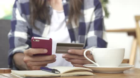 Young female hands buying goods from the internet on smartphone with credit card