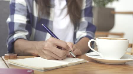 Close up of a Woman sitting and writing in her journal Vídeos