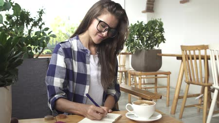 Stylish young girl writes in the diary in cafe