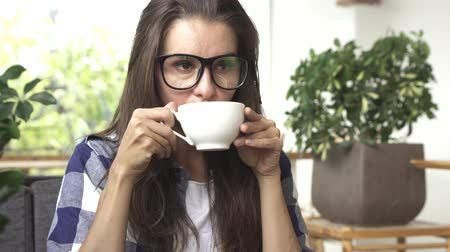 Woman drinking coffee and smiling.