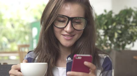 szemüveg : Woman using mobile cell smart phone laughing wearing glaasses and drink coffee Stock mozgókép