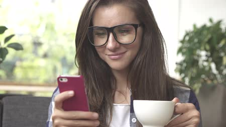 Businesswoman with smartphone drinking coffee