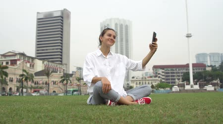 Tourist take photos and selfies on grass in Kuala Lumpur