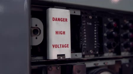 Danger high voltage sign. Old telephone dial station