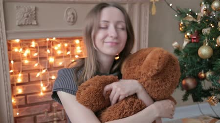 maci : Young woman sitting on the floor and hugs, toss, touch a big teddy bear in Christmas decorations, HD Stock mozgókép
