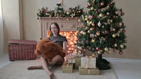 ursinho de pelúcia : Young woman sitting on the floor and hugs, toss, touch a big teddy bear in Christmas decorations, HD Vídeos