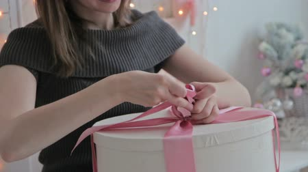 подарок : Happy young woman tie in a bow on Christmas present box, HD