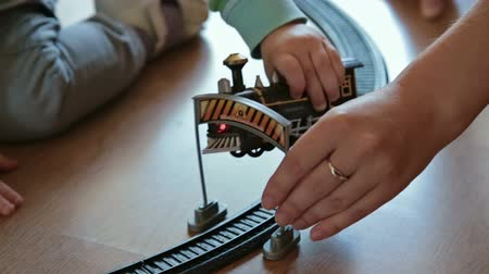 exercício : Little boy with mother playing with toy train