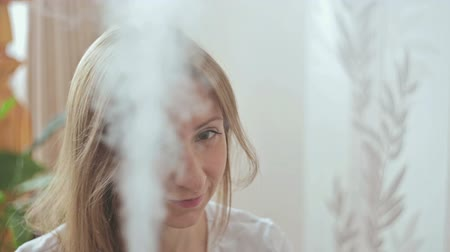 ionizing : Steam of humidifier and smiling womans face