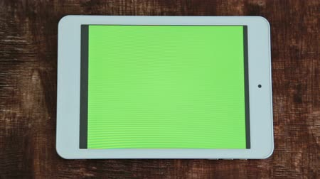 publicity : digital tablet computer with green screen on table