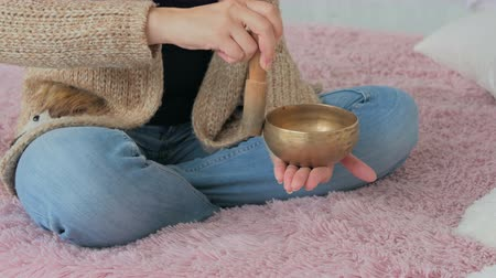 miska : Young woman in cardigan relaxing with nepal singing bowl. Meditation and relax concept
