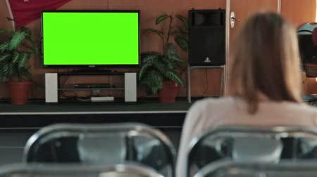 tv screen : Woman watching TV with green screen in the empty conference hall of cruise ship