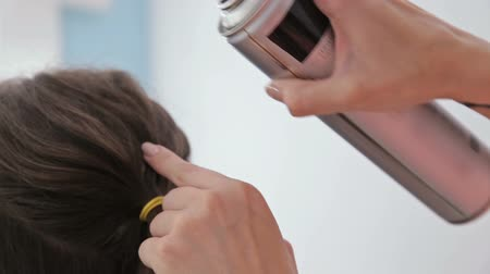 pulverização : Close up shot. Professional hairdresser doing hairstyle for young pretty woman and using hair spray