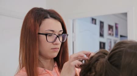 застежка : Hairdresser finishing hairstyle for young pretty woman