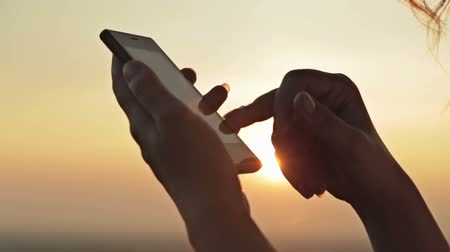 hipster : Woman hands with smartphone at sunset