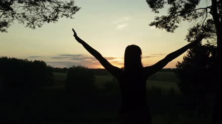 braços levantados : Happy young woman silhouette against sky lifts hands up in air