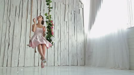 swing : 2 shots. Pretty, young and sensual woman with beautiful make-up and elegant hairstyle on a swing decorated with flowers blowing bubbles
