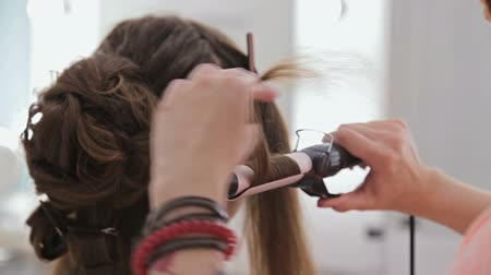 curling hair : Close up shot. Professional hairdresser doing hairstyle for young pretty woman - making curls