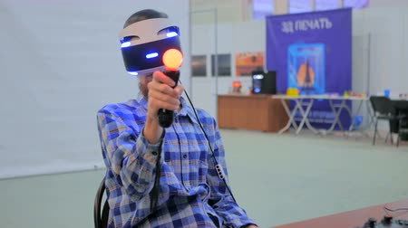 playstation : NIZHNIY NOVGOROD, RUSSIA - JANUARY 28, 2017: Exhibition of modern technologies. Virtual reality game. Young man using virtual reality glasses. Sony PlayStation VR Stock Footage