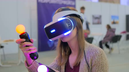 fejhallgató : Exhibition of modern technologies. Virtual reality game. Young woman using virtual reality glasses. VR