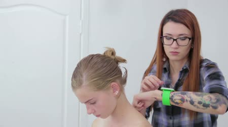 застежка : Professional hairdresser, stylist doing hairstyle for teen girl and using barrette for fixing hairdo in white make up room. Beauty and haircare concept Стоковые видеозаписи
